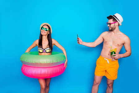 Guy in the hat, sunglasses and bright shorts holding a cool cocktail and taking pictures of a happy girl with multi-colored inflatable circles on the smartphone Foto de archivo