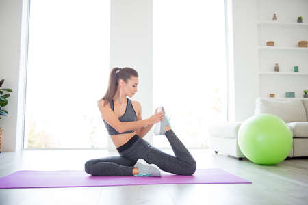 Build muscle day sun light window flat apartment concept. Pretty confident attractive beautiful lady with ponytail hairstyle stretching knees holding shoes sitting on purple carpet Stok Fotoğraf