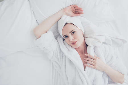 Young cute adorable attractive mature smiling woman lying in bed on white sheets and pillow wearing bathrobe and turban enjoying.  Top above high angle veiw