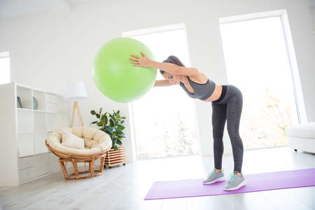 Wellness wellbeing practice white spacious domestic room vitality concept. Beautiful sporty sportive active energetic woman in bra and leggings incline with green fitness ball standing on purple mat Imagens