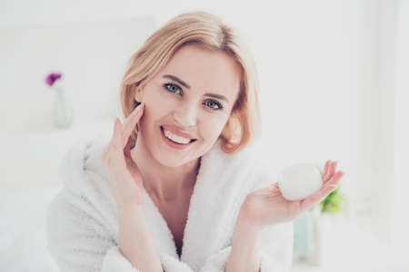 Closeup portrait of adult beautiful attractive blonde cute mature smiling woman wearing white bathrobe spreading face lotion cream gel on her face. Keeping and showing cream jar in other hand