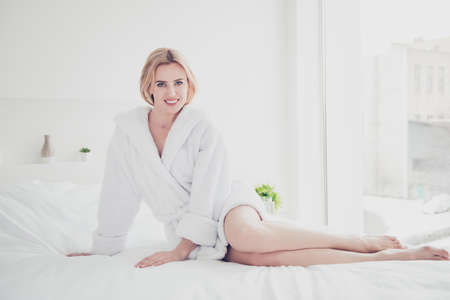 Young cute smiling blonde woman in bed on white sheets and blanket wearing white bathrobe in bedroom with white interior. Healthcare