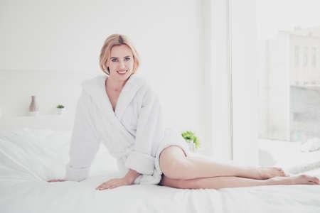 Giovane donna bionda sorridente carina a letto su lenzuola bianche e coperta indossando accappatoio bianco in camera da letto con interni bianchi. Assistenza sanitaria
