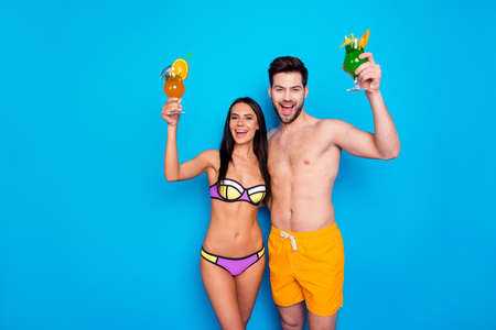 Beautiful young girl in swimsuit and handsome man in yellow shorts happily shout out a greeting and raise glasses with drinks up! Couple rest guys on blue background with place for text Banco de Imagens