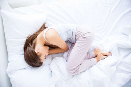 Top view portrait of sleepy woman in embryo position wearing pants sleeping after hard day having sweet dreams