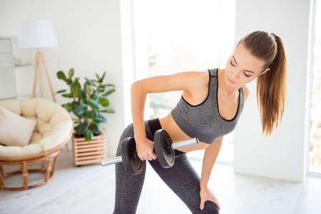 I adore love my hobby! Good day morning power for doing strength exercise! Close up photo of tender gentle beautiful muscular skinny lady holding heavy dumbbell in palm wearing gray tight sport suit Banco de Imagens