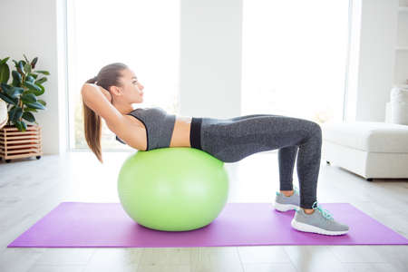 Vitality wellness healthy lifestyle gym club group people person model concept. Side profile full-length view photo portrait of sporty sportive beautiful purposeful determined girl doing sit-ups Stock Photo