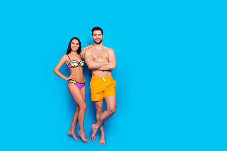 Full-length shot with slim girl in a separate swimsuit laid her hand on shoulder to guy in yellow shorts. The concept of summer vacation, isolated image on a blue background with copy space