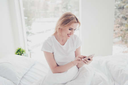 Young charming cute smiling blonde woman awake in bed on white sheet covered with blanket wearing t-shirt in bedroom with white interior texting sms on cell-phone. Big window on background