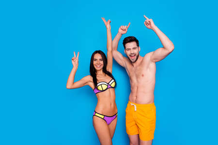 Party mood! Handsome brunette and attractive young woman celebration vacation time with rise hands up and make v-sign isolated on blue background