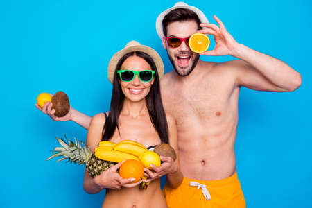 Handsome couple in in a good mood and colourful eyewear holding a lot of fruit. Funky young woman and handsome men messing around with fruit