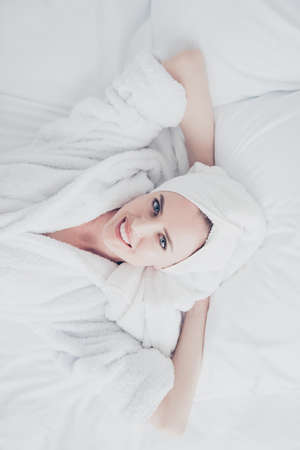 Cute adorable attractive mature woman smiling with her teeth lying in bed on white sheets and pillow wearing bathrobe and turban enjoying. Top above high angle veiw