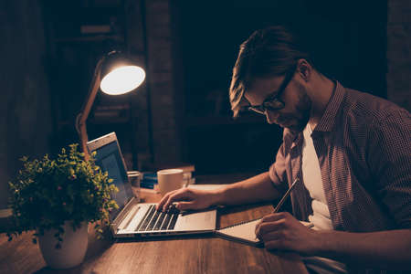 Side view portrait of attractive, busy, smart man in shirt with stubble making notes on notepad with pencil, holding arm on keypad, working at night time, sitting in work place, station