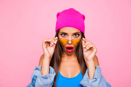 WOW! Close up portrait of shocked girl face looks over the glasses directly at the camera isolated on bright pink background Archivio Fotografico