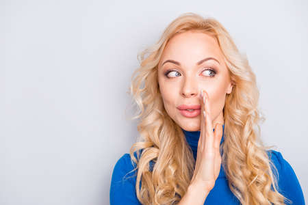 Portrait of pretty, trendy, charming, lovely, nice, sexy, cute, blonde woman in blue turtleneck isolated on grey background cover mouth with palm looking to the side whispering gossips