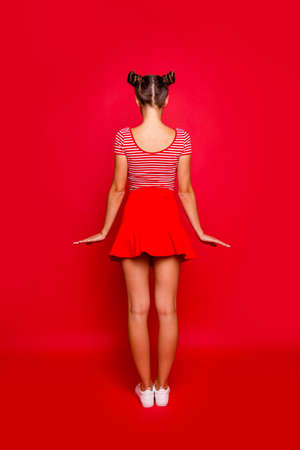 Full-legh full-size portrait of a young girl standing with her back to the camera on a bright red background