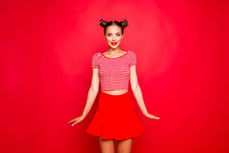 Adorable fancy young girl wear in red skirt and striped tshirt stand upright look at the camera isolated on red backgroung 写真素材 - 106121669