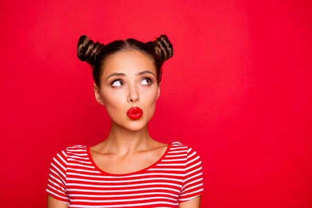 Attractive young girl with nice make up wearing striped tshirt puffed up her lips and looked up isolated on bright red background with copy space Reklamní fotografie