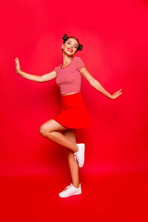 Full-legh and full-body vertical photo of charming, lovely and cute young woman isolated on red vivid background Reklamní fotografie