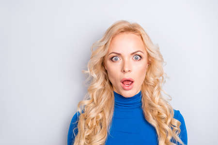 Portrait of sexy, scared, impressed, shocked, stylish, pretty, cute, charming, nice, blonde woman in blue turtleneck  with wide open eyes and mouth looking at camera Standard-Bild