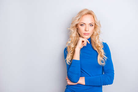 Portrait with copy place, empty space of sexy, cheerful, stylish, pretty, cute, charming, nice, blonde woman in blue turtleneck holding hand near chin looking at camera isolated on grey background