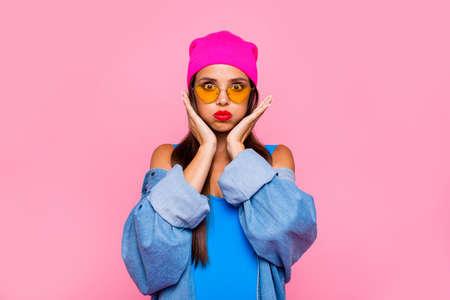 Close Up retrato de niña divertida, tonta y joven infló sus mejillas y sosténgalas con sus manos aisladas sobre fondo rosa vivo