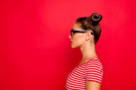 Half-faced side profile view portrait of serious and confident young woman in striped shirt and spectacles isolated on red vivid background with copy space