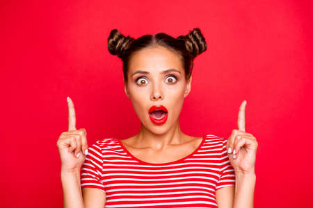 Close up portrait of astonished girl with wide open mouth gesturing index fingers up isolated on red background. Advertisement concept Stock Photo
