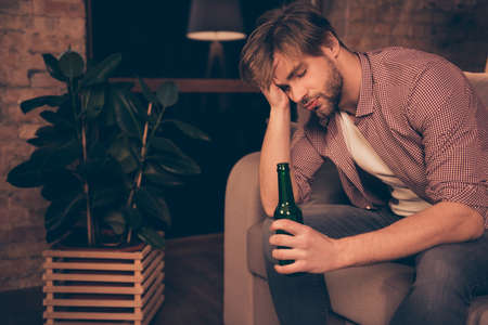 Portrait of unlucky, upset, tired, attractive, frustrated man holding bottle of beer in hand touching his head with arm having close eyes, bad luck, alcohol addiction, relationship problems Stock Photo
