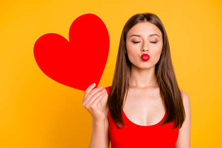Portrait of charming woman with big paper carton red heart in hand waiting a kiss isolated on yellow vivid background Фото со стока