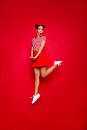 Full-length full-size vertical view of jumping and wondered brunette woman dressed in colourful bright clothes isolated on red background