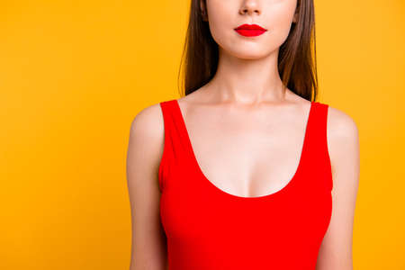 Close up half face portrait of confident brunette woman with red lips in vivid swimsuit isolated on bright yellow background Stock Photo