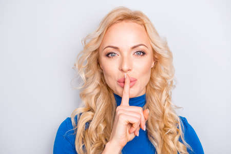 Shhh! Portrait of pretty, trendy, charming, lovely, nice, sexy, cute, blonde woman in blue turtleneck isolated on grey background showing silence sign with forefinger looking at camera