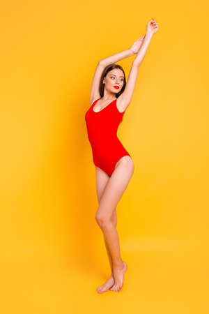 Pool party time! Full-legh vertical portrait of  charming brunette in red swimsuits with hands up looks dreamily away isolated on vivid yellow background