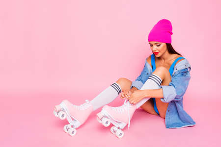 Attractive girl in stockings on roller skates ties up the shoelaces isolated on bright pink background Stock Photo
