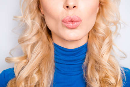 Cropped, close up, half face portrait of pretty, trendy, charming, lovely, nice, sexy, cute, blonde woman in blue roll neck isolated on grey background sending air kiss with pout lips to the camera Stockfoto