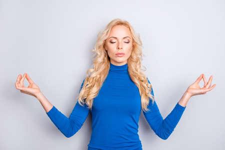 Retrato de mujer sexy, alegre, elegante, bonita, linda, encantadora, agradable, rubia con cuello alto azul sosteniendo y dedos en posición meditativa con ojos cerrados aislados sobre fondo gris
