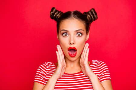 Sag was? Schließen Sie herauf Porträt des schockierten brünetten Mädchens mit weit offenem Mund und großen Augen halten Handflächen nahe Gesicht lokalisiert auf rotem lebendigem Hintergrund