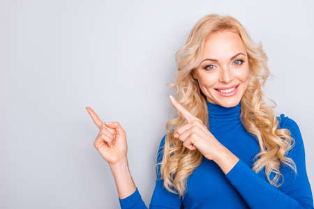 Portrait with empty place of stylish, pretty, charming, nice, sexy, cute, blonde woman in blue roll neck pointing two forefingers to copy space isolated on grey background looking at camera