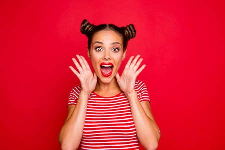 ŁAŁ! Portret zaskoczony dziewczyna z szeroko otwartymi ustami, gestykuluje z dłońmi w pobliżu twarzy na białym tle na czerwonym tle
