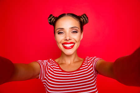 Video call of pretty, charming and smiling young girl with modern hairdo. Model shooting selfie on front camera with two arms isolated on red background Stock fotó