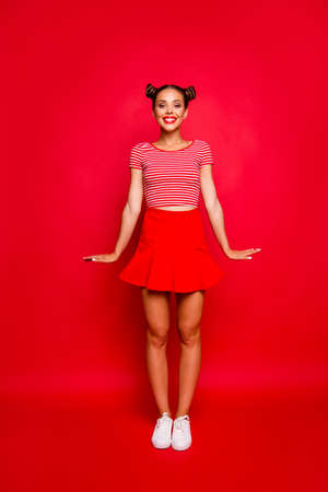 Full-length vertical portrait of happy young girl wear in red skirt and striped tshirt stand upright look at the camera isolated on red background 写真素材 - 106080250