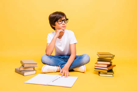 Thinking child frustrated surrounded by books and notebooks, doing his homework for the school isolated on yellow background