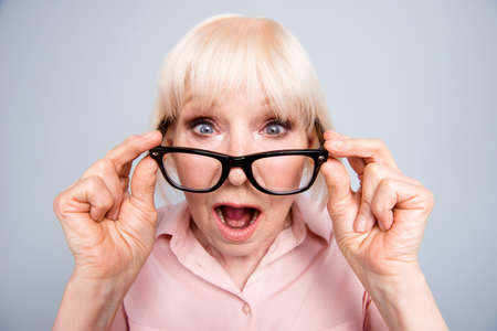 Portrait of old adult blonde caucasian lady shocked scared surprised wearing putting down eye glasses, over grey background, isolated Archivio Fotografico