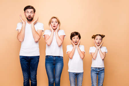Portrait of young surprised family, bearded father, blonde mother and their little children wearing jeans and white T-shirts, standing straight and gesturing unsurely placing palms to cheeks