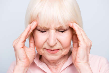 Close up portrait of old adult lady feeling head ache, pain, high blood pressure facial expression, on grey background, isolated