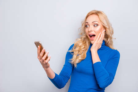 Portrait of pretty, trendy, charming, nice, sexy, cute, shocked, impressed woman having smart phone in hands looking at screen of device with wide open eyes and mouth holding hand on cheek Foto de archivo - 107035010