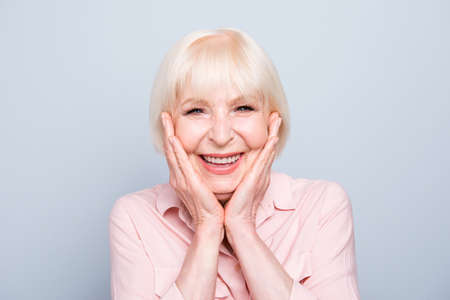 Old adult blonde glad excited cheerful astonished lady smiling, laughing, palms to cheeks, over grey background, isolated