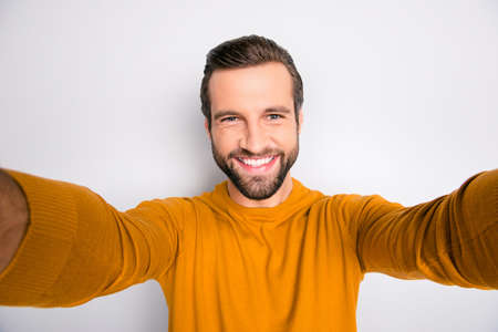 Self portrait of handsome flirty man with toothy beaming shiny smile taking making self picture on his new updated smartphone isolated on gray background Stock Photo