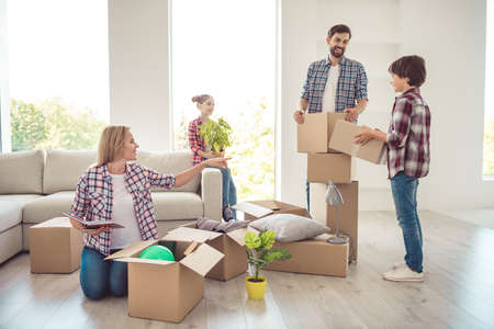 Young happy smiling family four persons unwrapping carton boxes with stuff in light studio living room, moving to new flat, check list